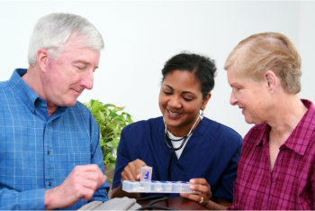 elderly couple and a caregiver holding a medicine kit